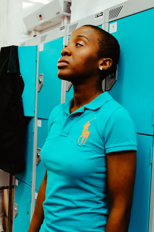 Woman Wearing Blue Us Polo Assn Polo Shirt in Front of Locker