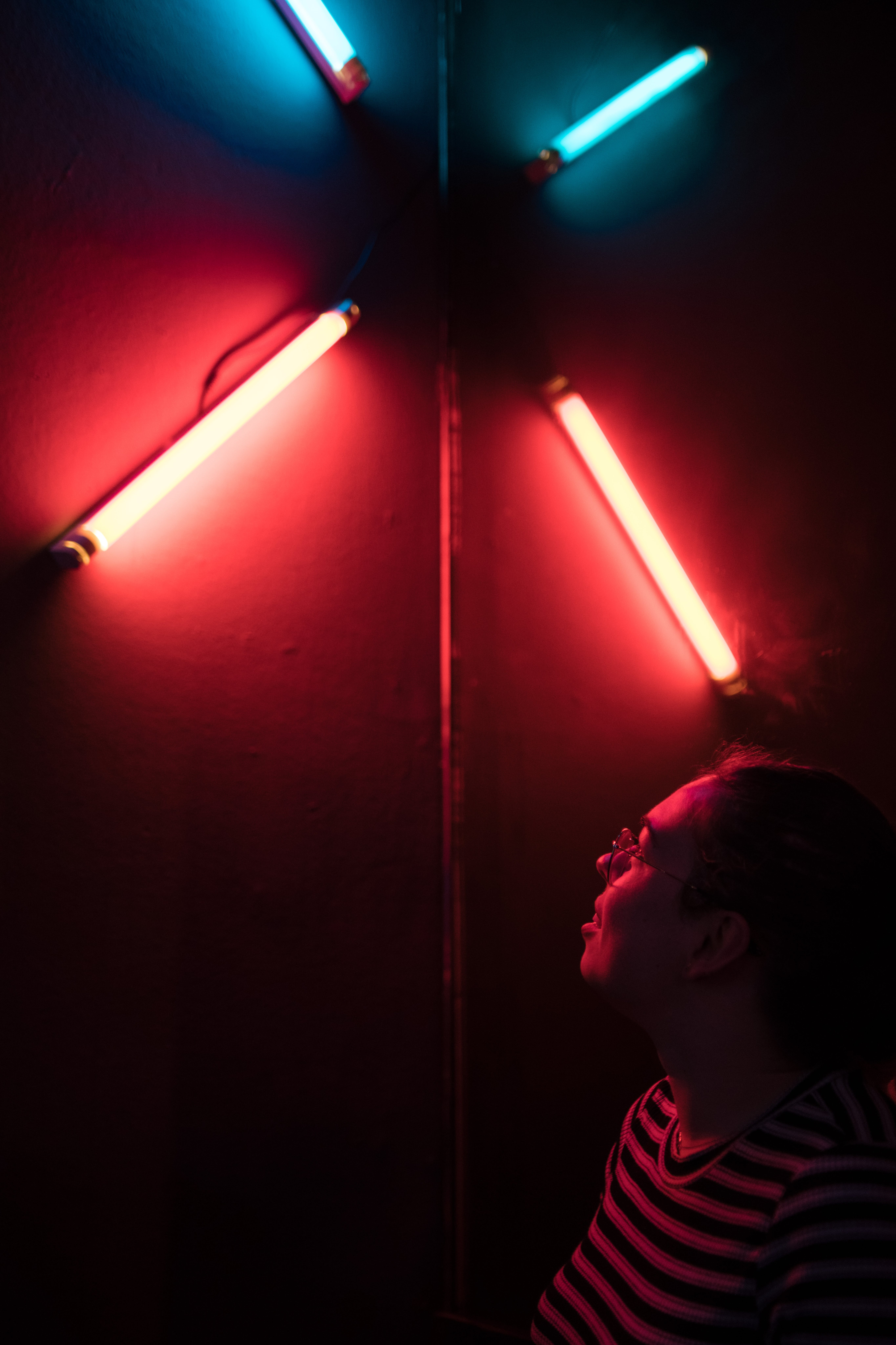 Man Looking Beside Four Red and Blue Led Lamps