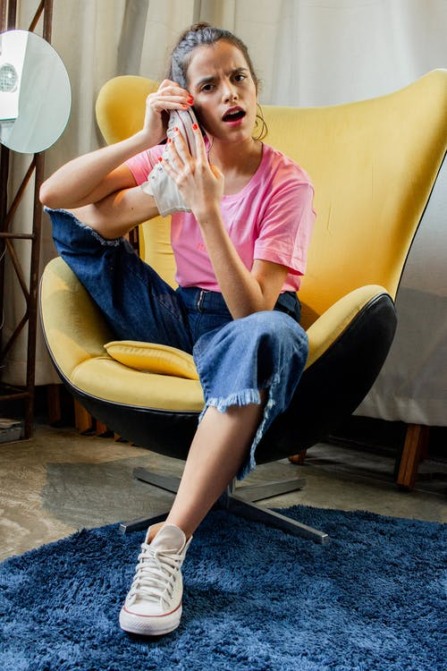 Woman Sitting on Egg Chair Putting Her Foot on Her Face