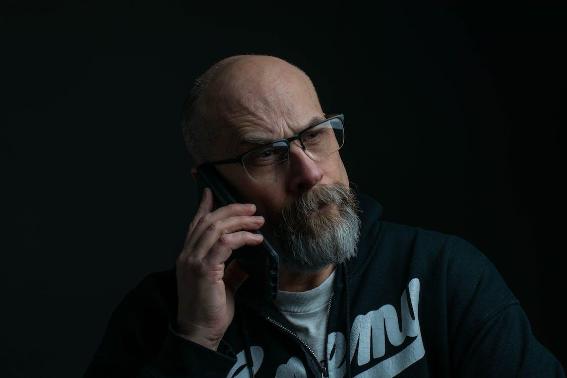 Man Holding Phone And Wearing Eyeglasses