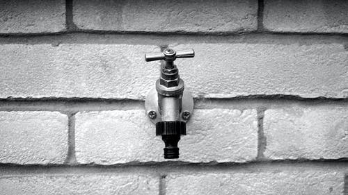 Grayscale of Metal Faucet on Wall Brick