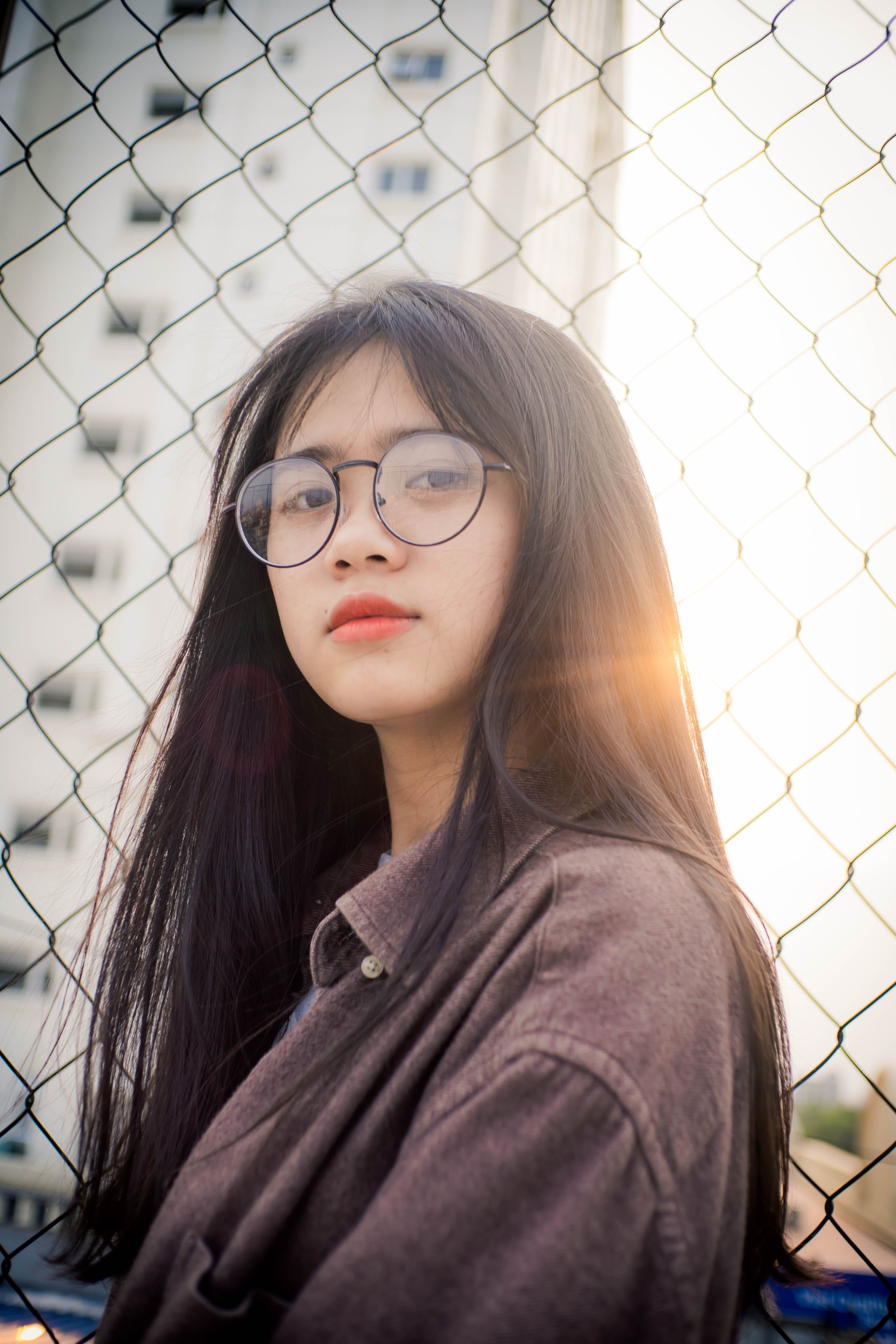 Photo of Woman in Glasses Standing by Chain Link Fence