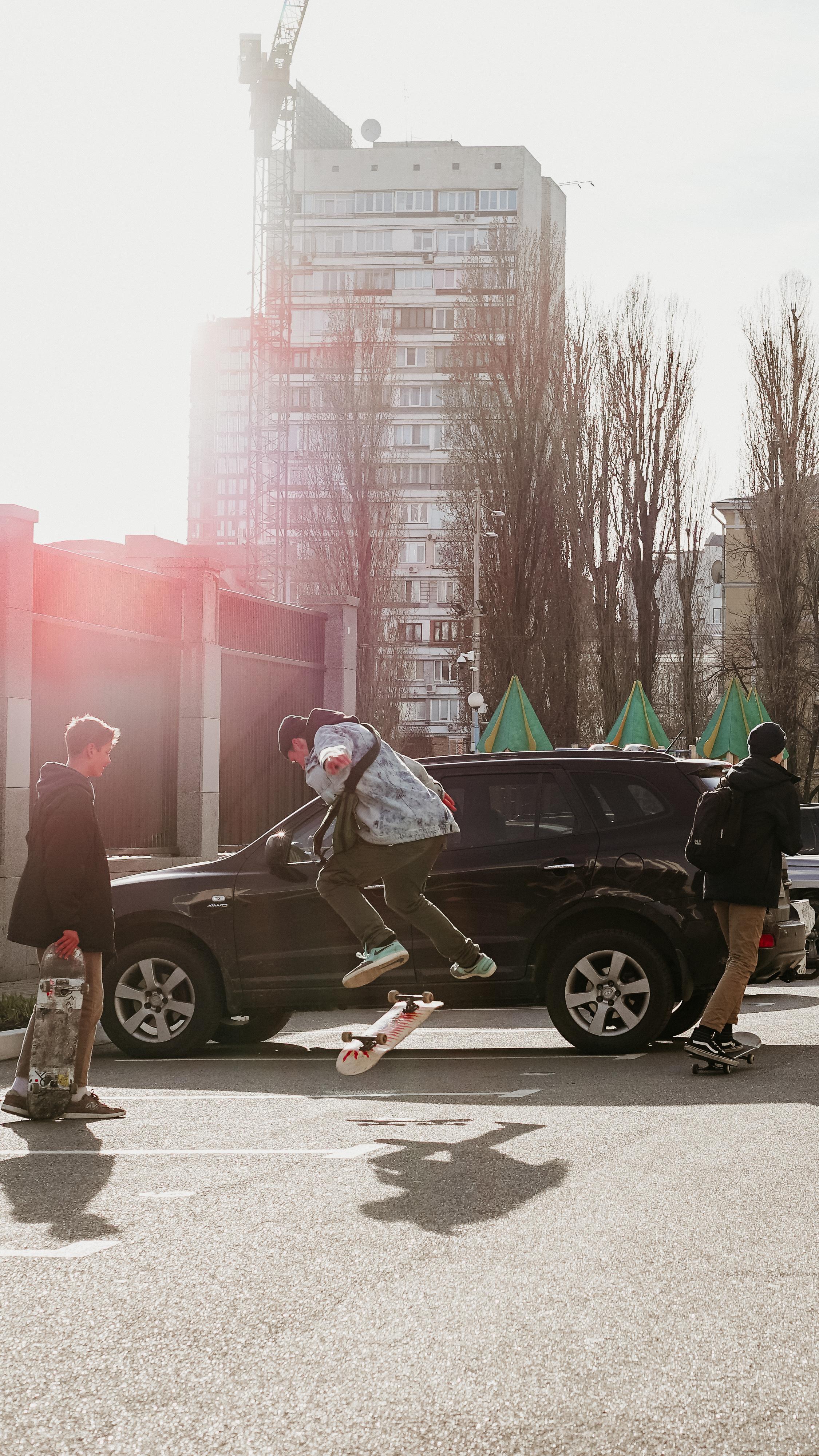 Man Jumping over Skateboard Beside Vehicle