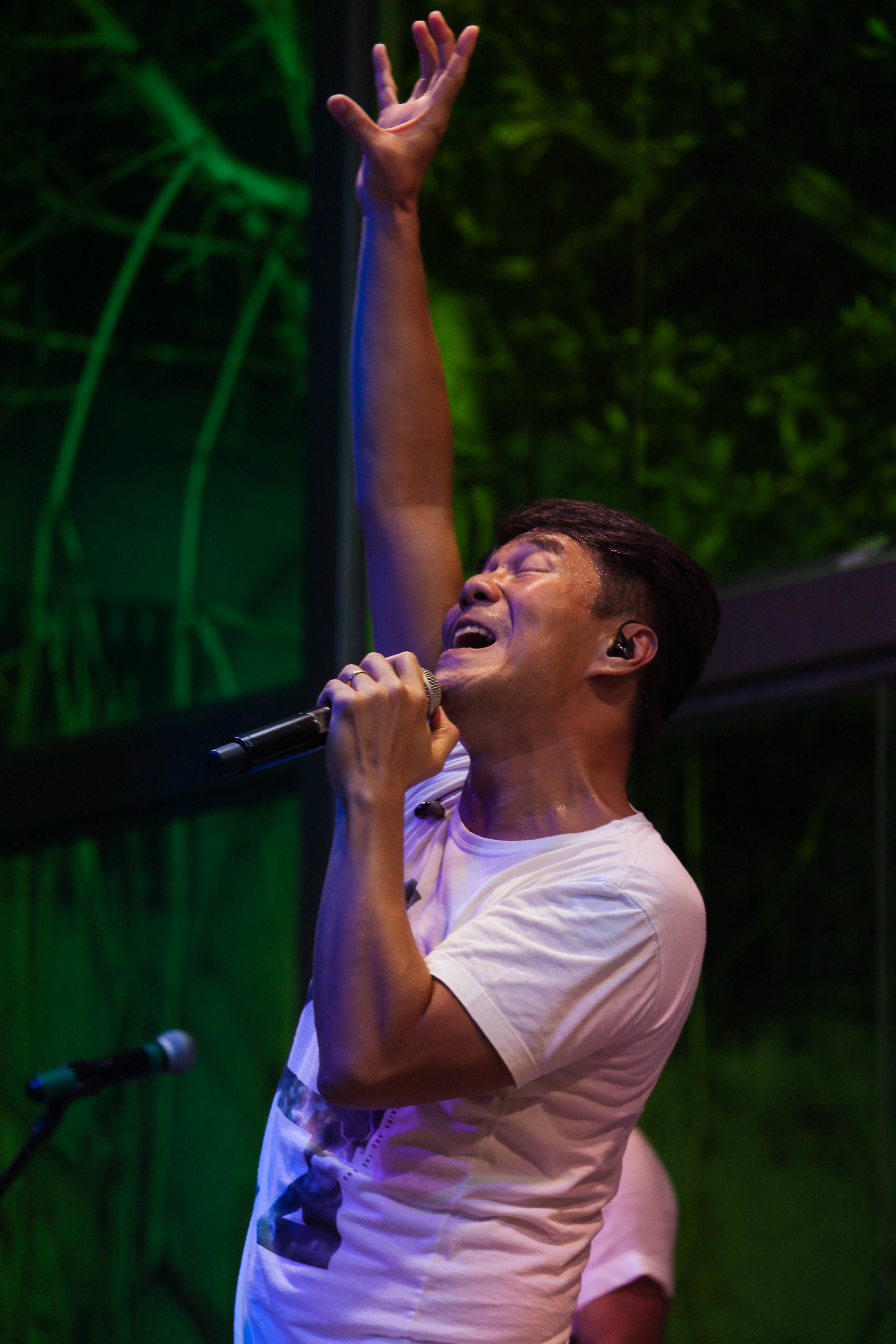 Man Wearing White T-shirt Singing at the Stage