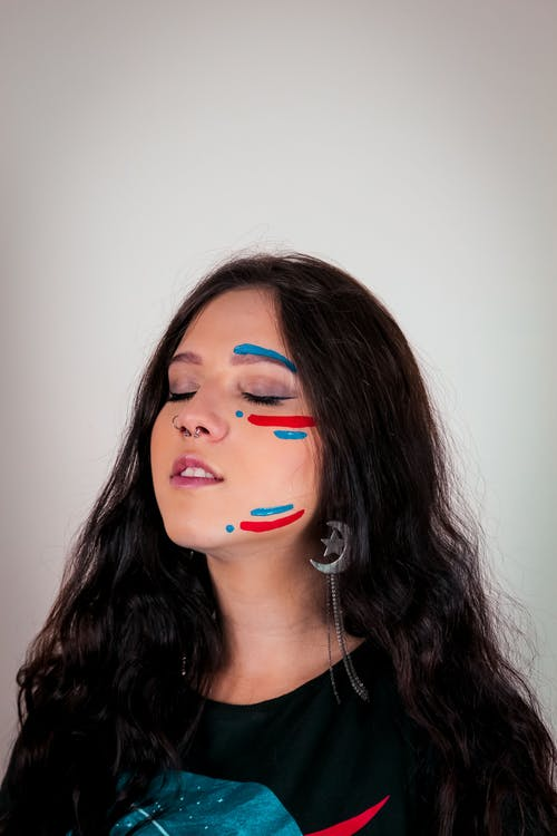 Portrait Photo of Woman With Face Paint Posing With Her Eyes Closed