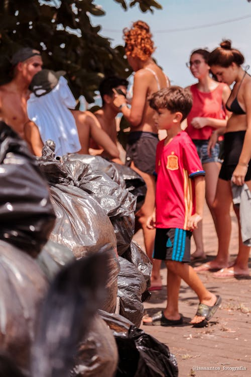 Boy in Red T-shirt Walking Beside Garbage Bags