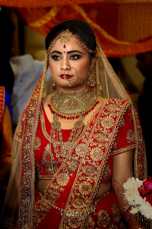 Woman Wearing Red and Gold Saree Wedding Dress