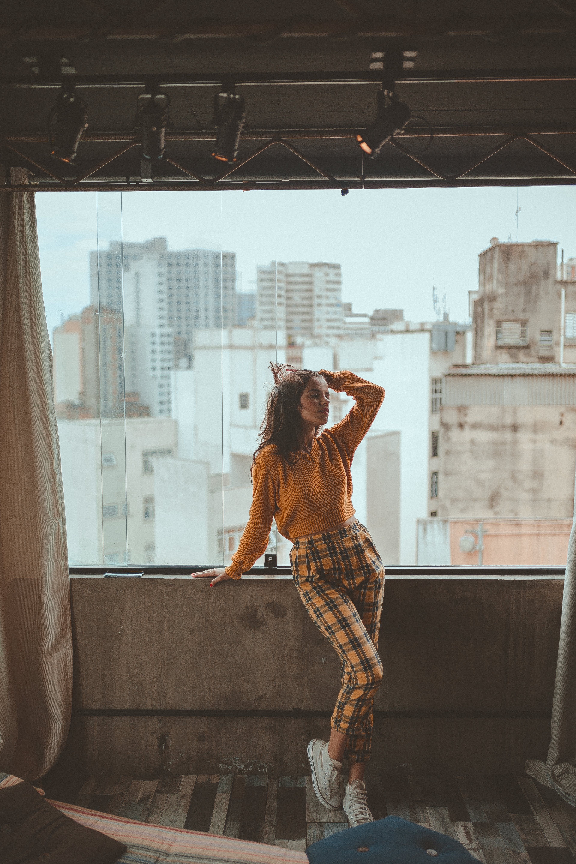 Woman Standing Beside Clear Glass Window