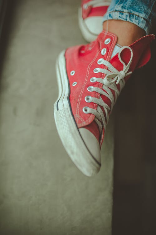 Close-Up Photo of Person Wearing Red Shoe