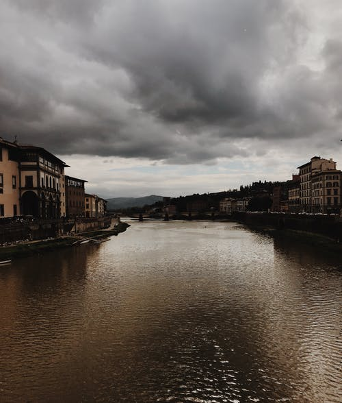 River Between Houses Under Dramatic Sky