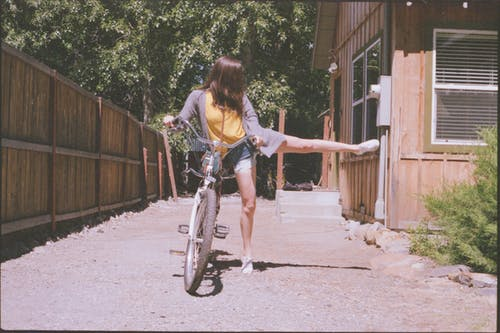 Woman Wearing Grey Cardigan Holding Bike
