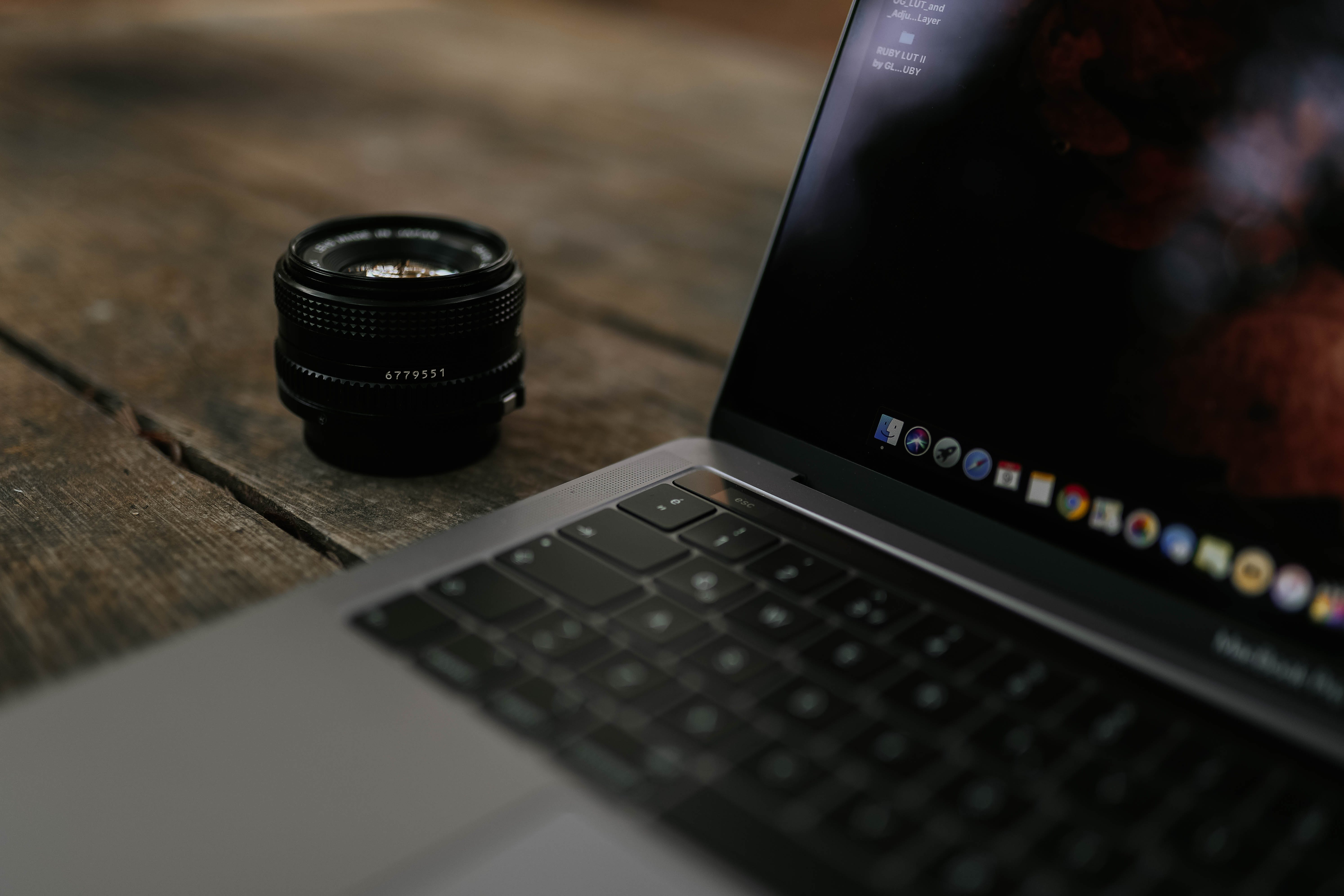 Shallow Focus Photography Of Black Zoom Lens Beside Macbook Pro