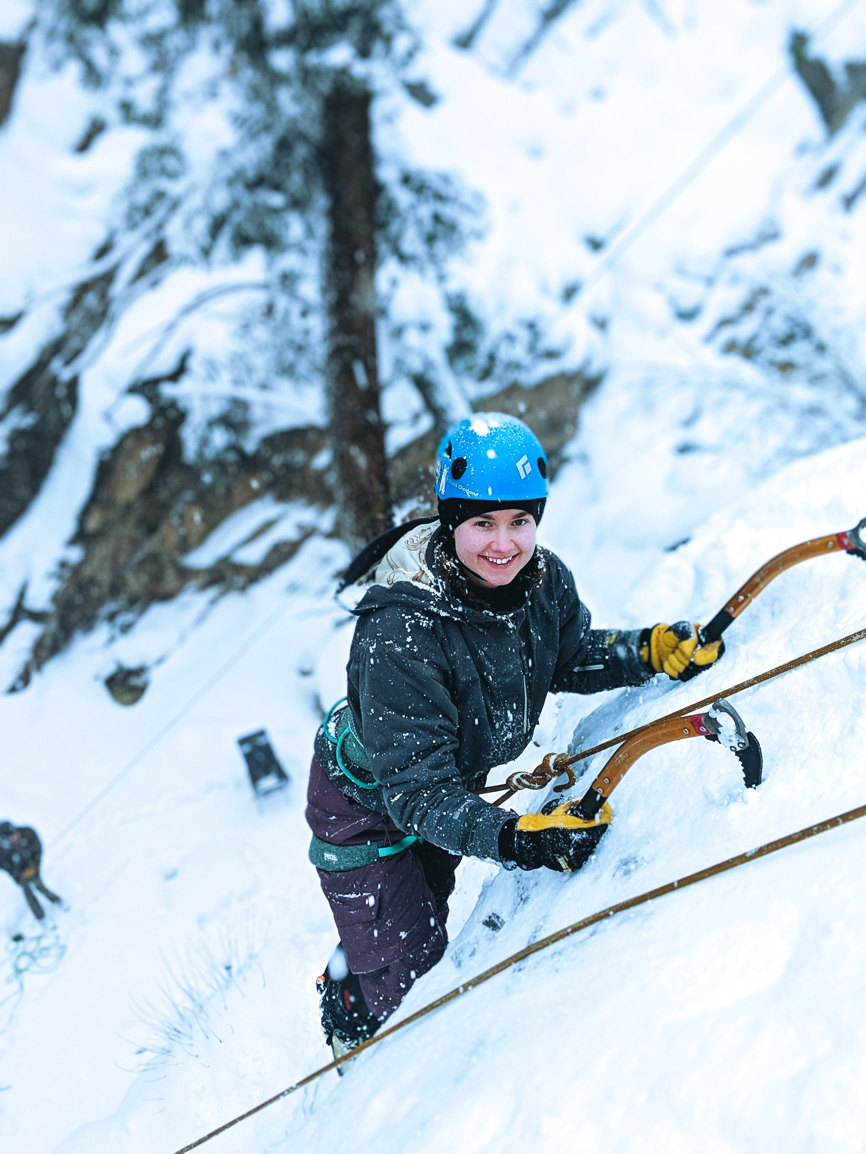 Girl Climbing Snowy Mountain Using Snow Hooks