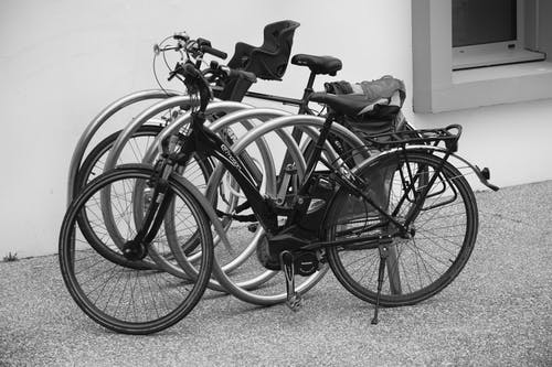 Black and Grey Bicycle Park Beside Wall