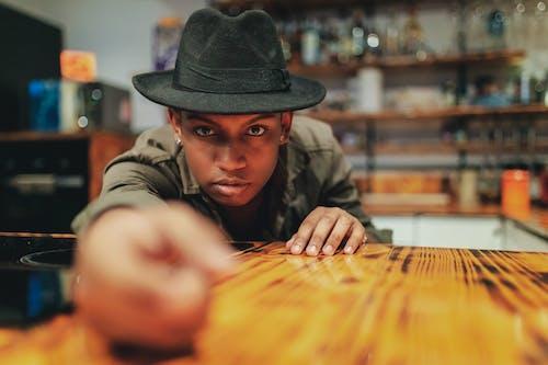 Безкоштовне стокове фото на тему «афроамериканський чоловік, всередині, дерев'яний стіл, капелюх»