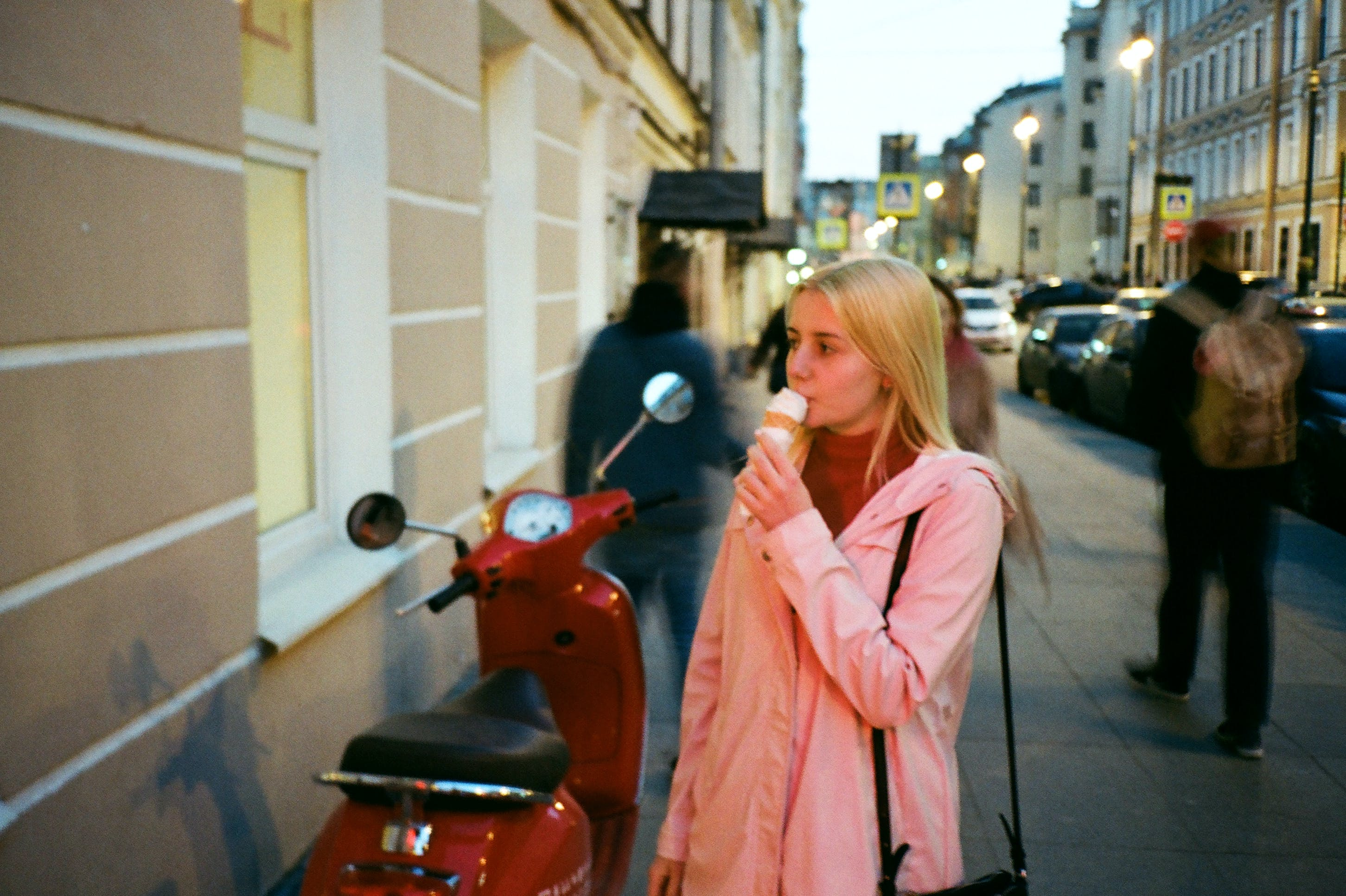 Photo of Woman Eating Ice Cream Near Red Motor Scooter by Side Walk