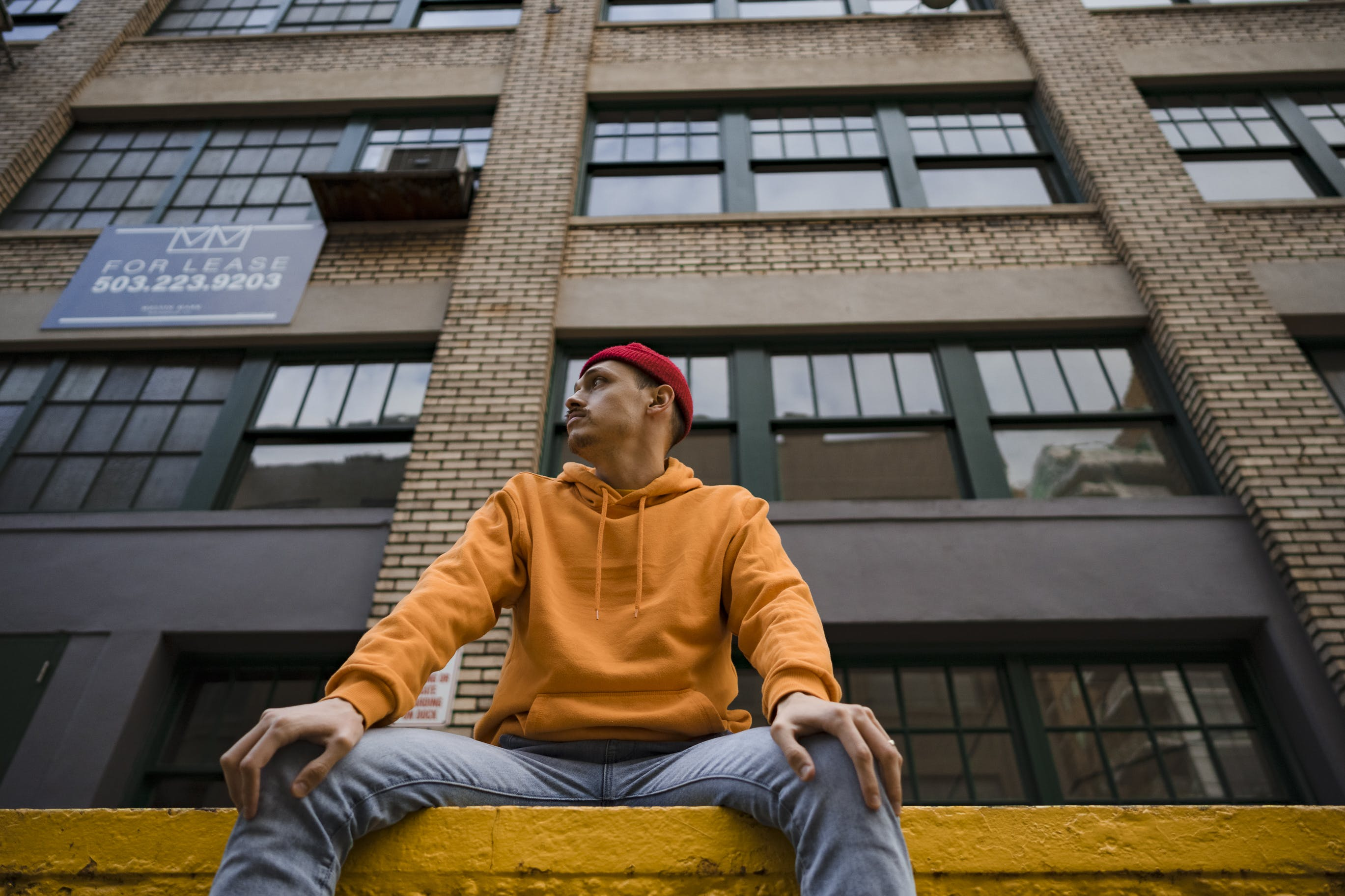 Man Sitting in Front of Brown High-rise Building