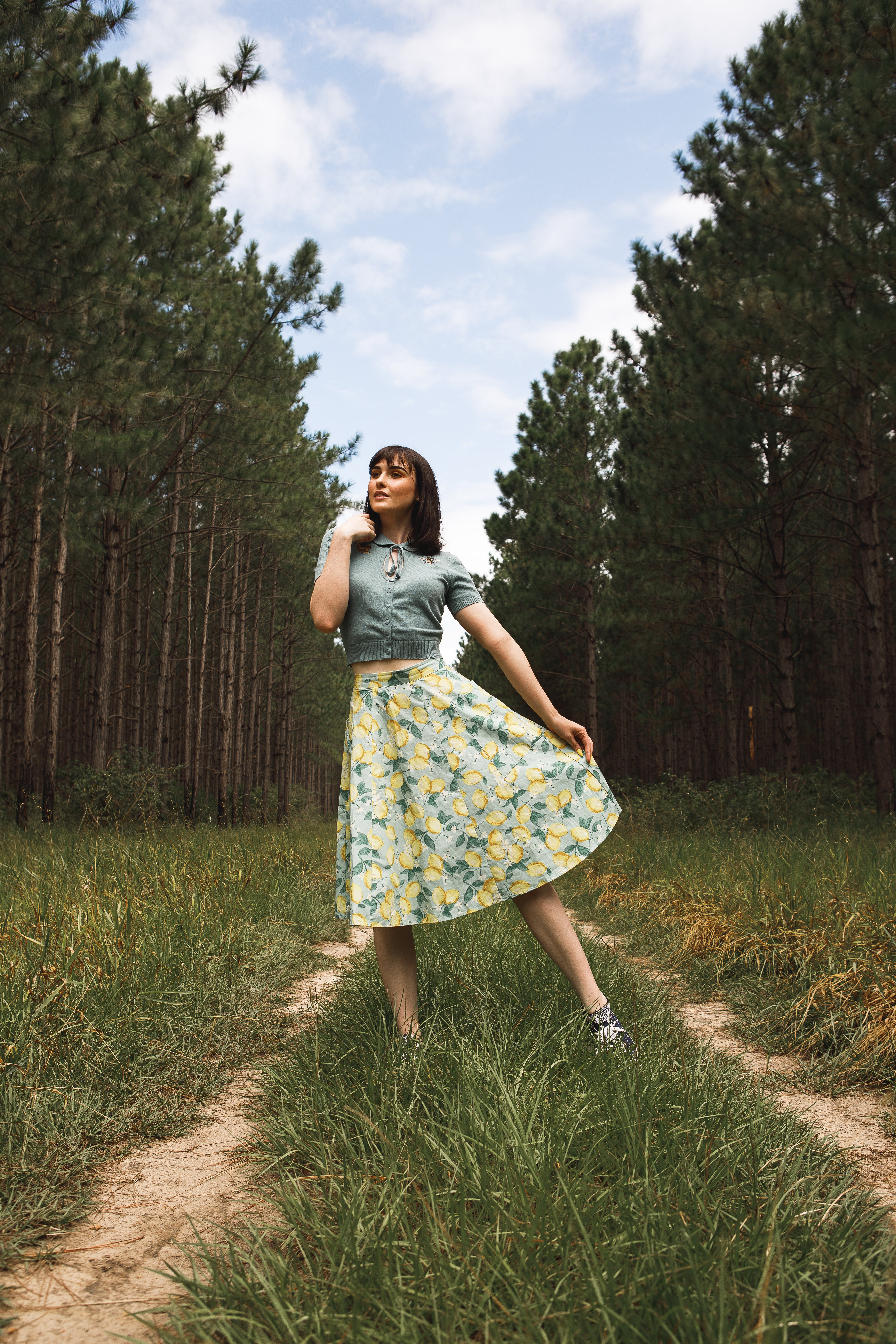 Woman Wearing Floral Skirt Standing On Grass Road