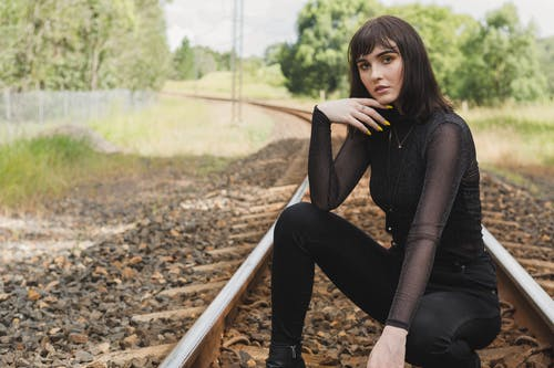 Photo of Woman in Black Outfit Squat Posing in Middle of Train Track