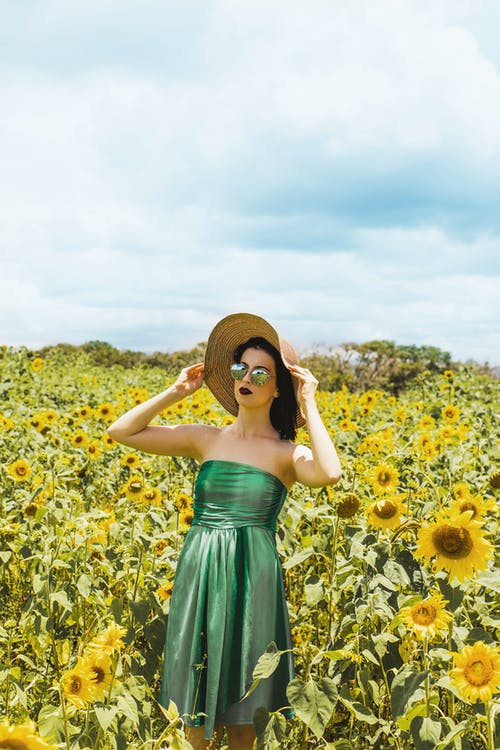 Woman Wearing Green Tube Dress And Sunhat Standing In The Middle Of Sunflower Meadow
