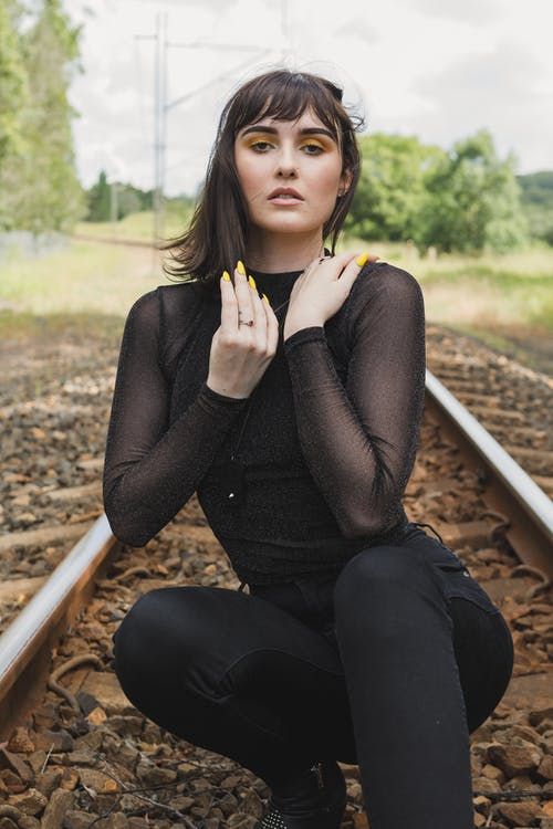 Woman Crouching On Train Track