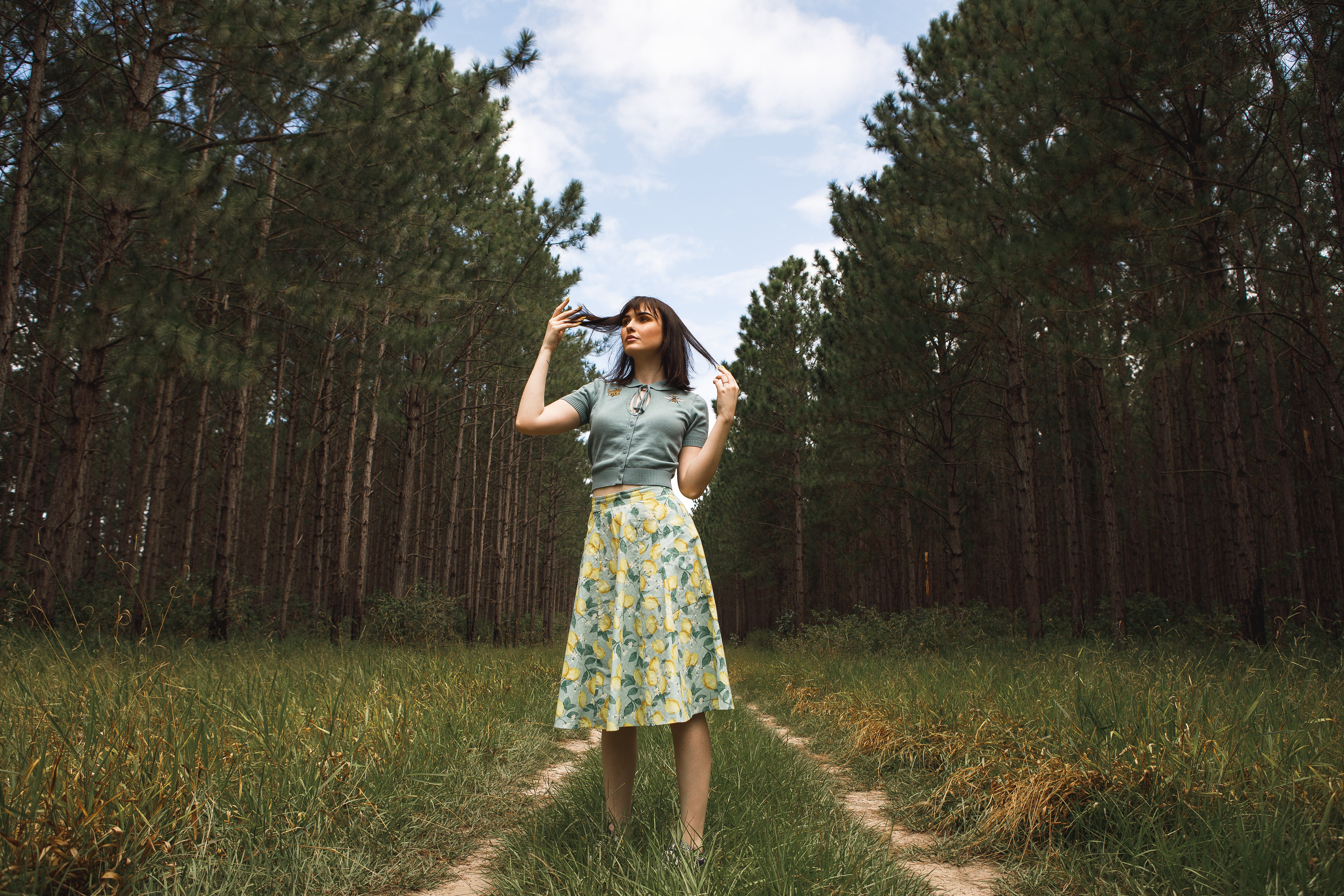 Standing Woman Wearing Blue And Yellow Floral Skirt
