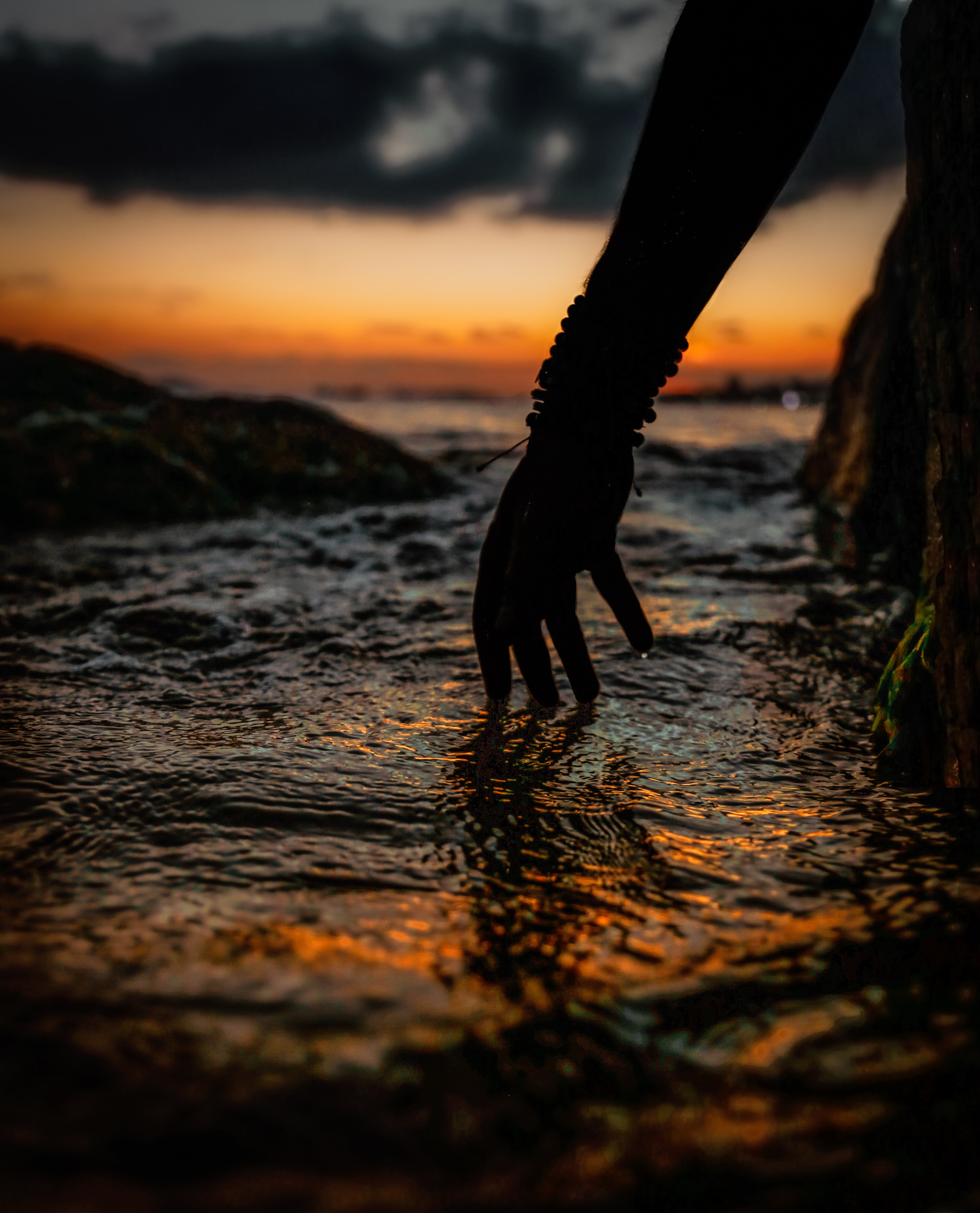 Silhouette of Person's Hand Touching Water during Sunset