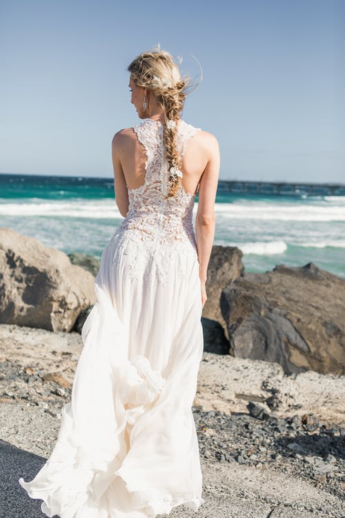 Woman In Wedding Gown Standing Near Body Of Water
