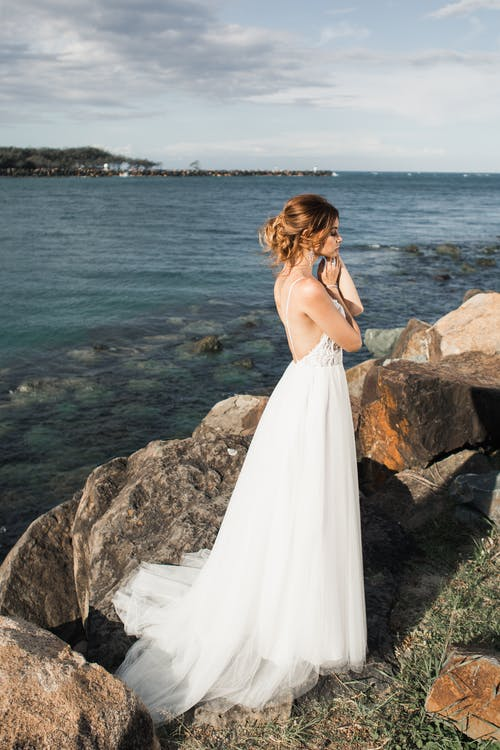 Woman In White Wedding Dress Standing On Rock