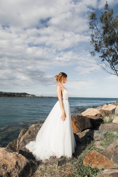 Woman Standing On Rocks Wearing White Wedding Dress Near Body Of Water