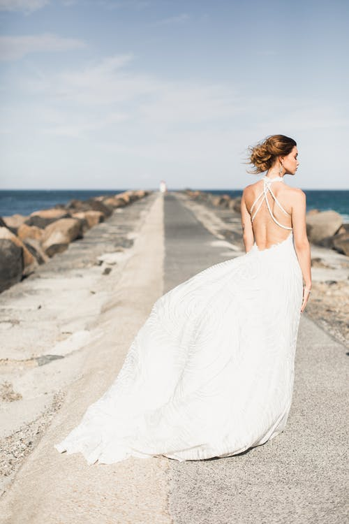 Woman Wearing White Backless Dress Standing On Concrete Boardwalk