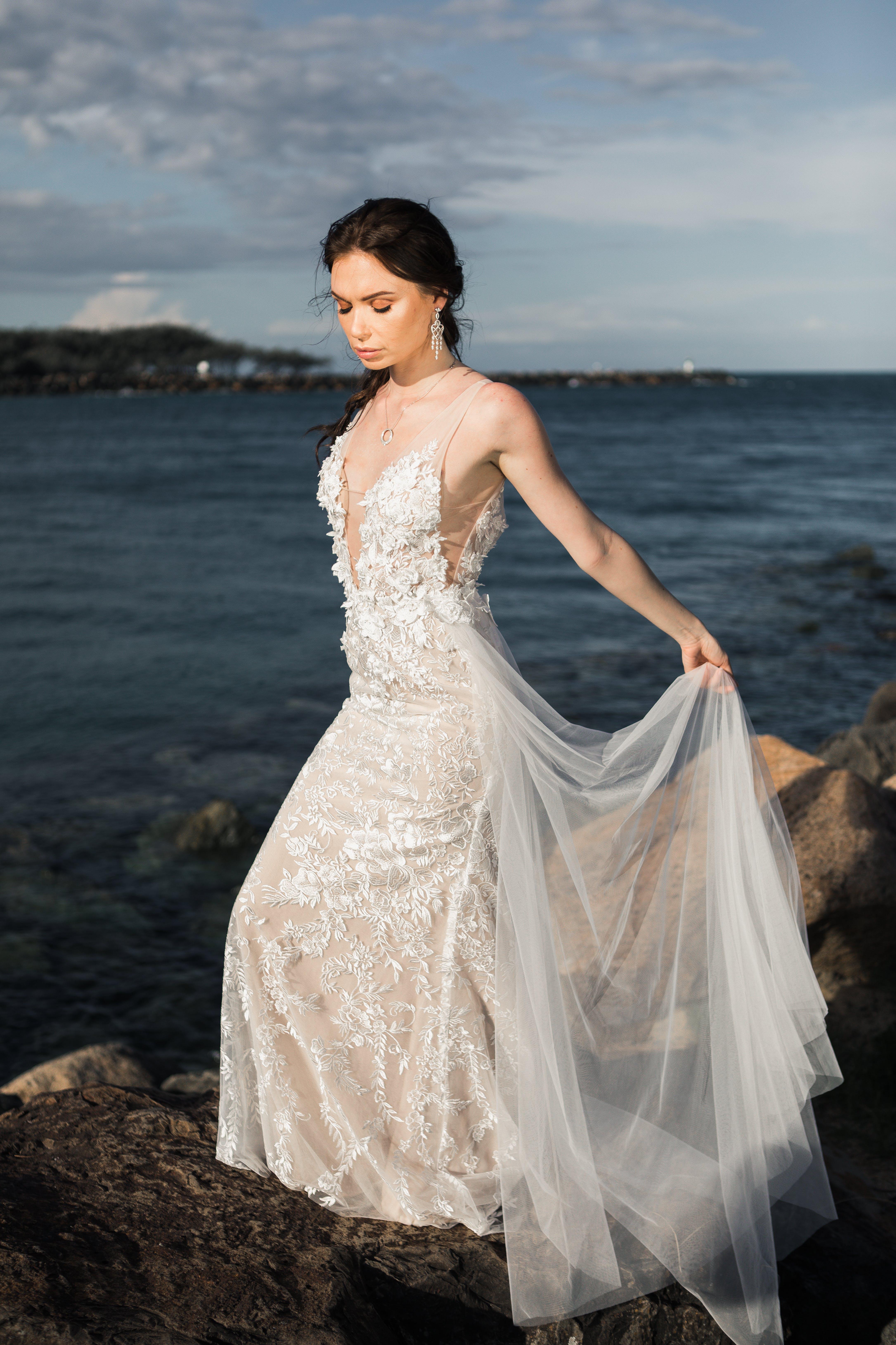 Woman Wearing White Floral Wedding Dress Standing On Rocks Near Body Of Water