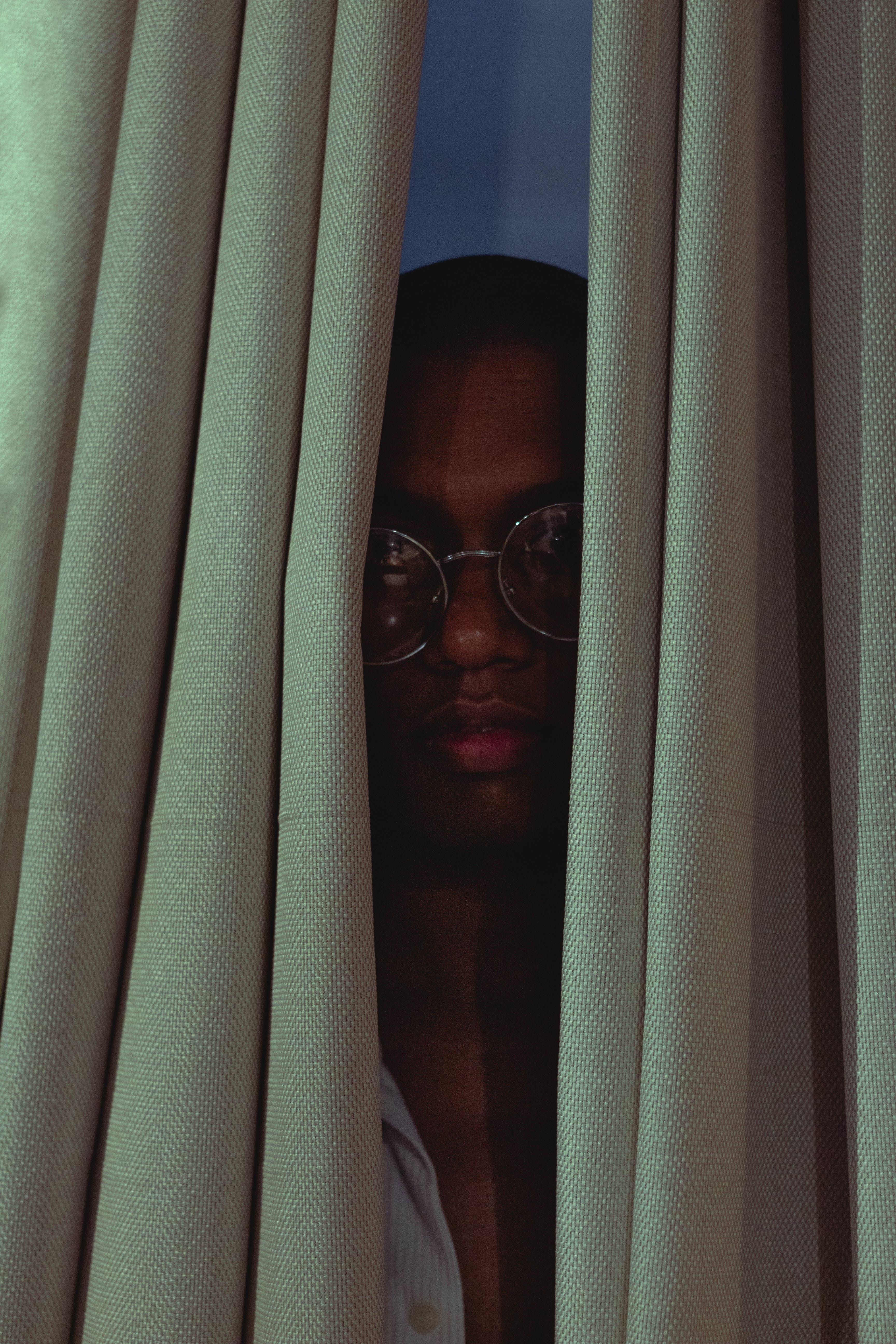 Man Hiding Behind Curtain