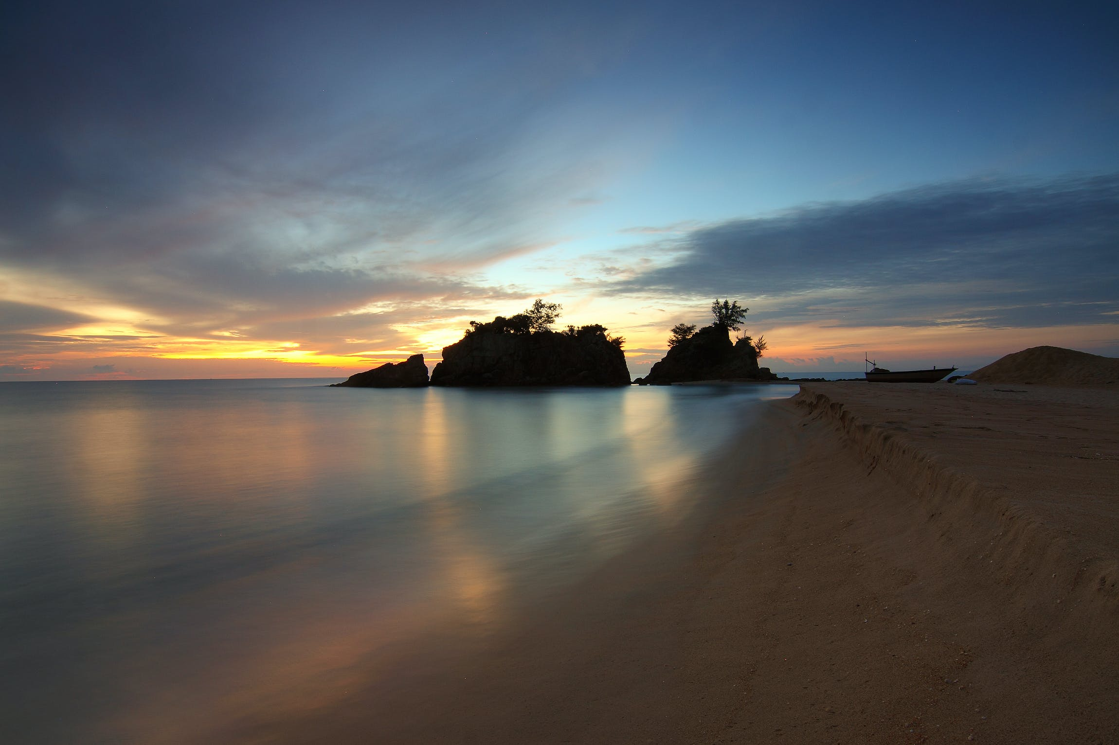 Calm Body of Water Near Shore With Silhouette of Rock Formation Against Setting Sun