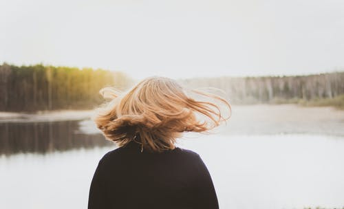 Back View Photo of Woman Flipping Her Hair While Looking at Lake