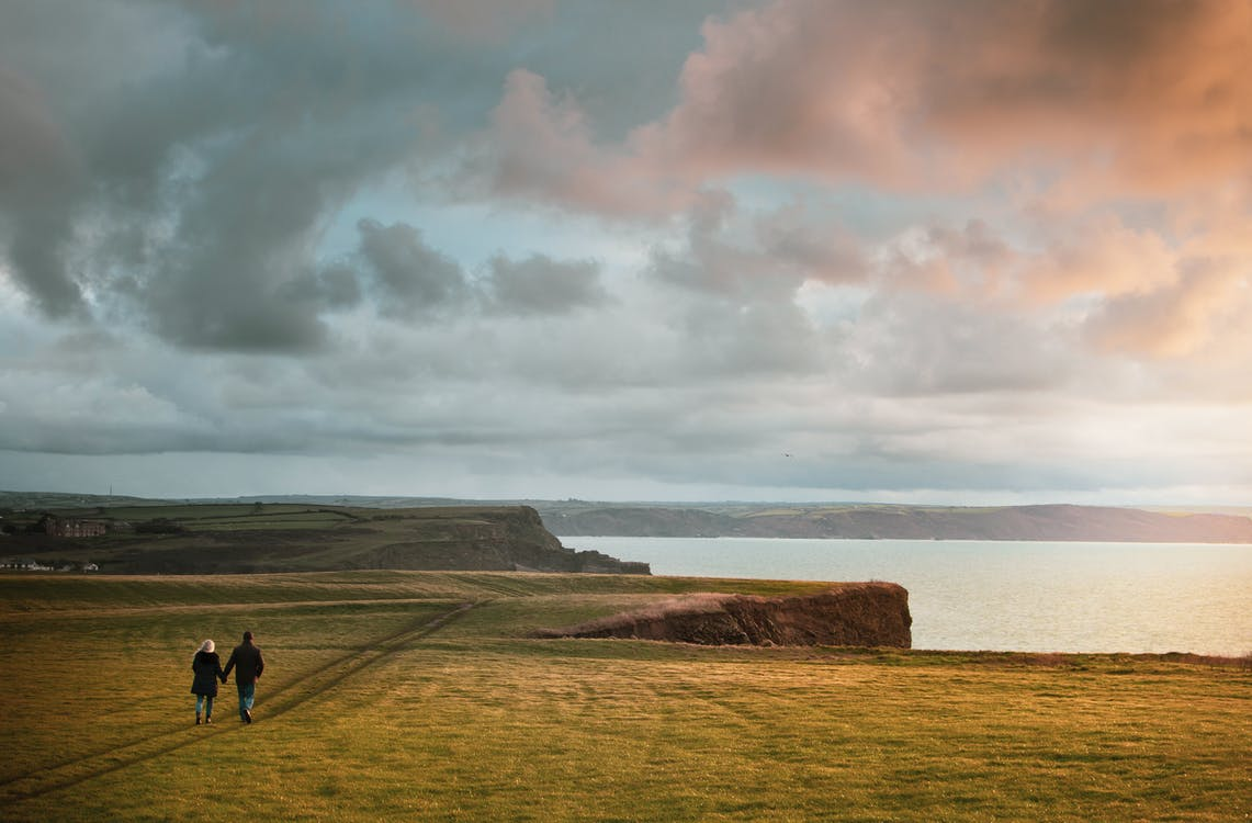 Man and Woman Walking on Gras