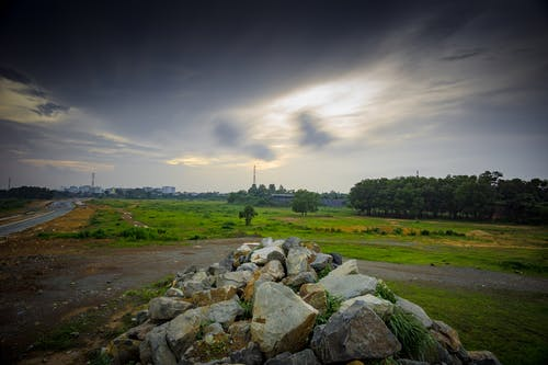Stratus Clouds Above Green Grass and Beige Stones