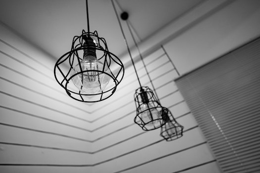 Black Steel Framed Round Pendant Lamp Indoors Near Window Blinds on Grayscale