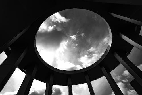 구멍이있는 둥근 건물의 회색조 사진