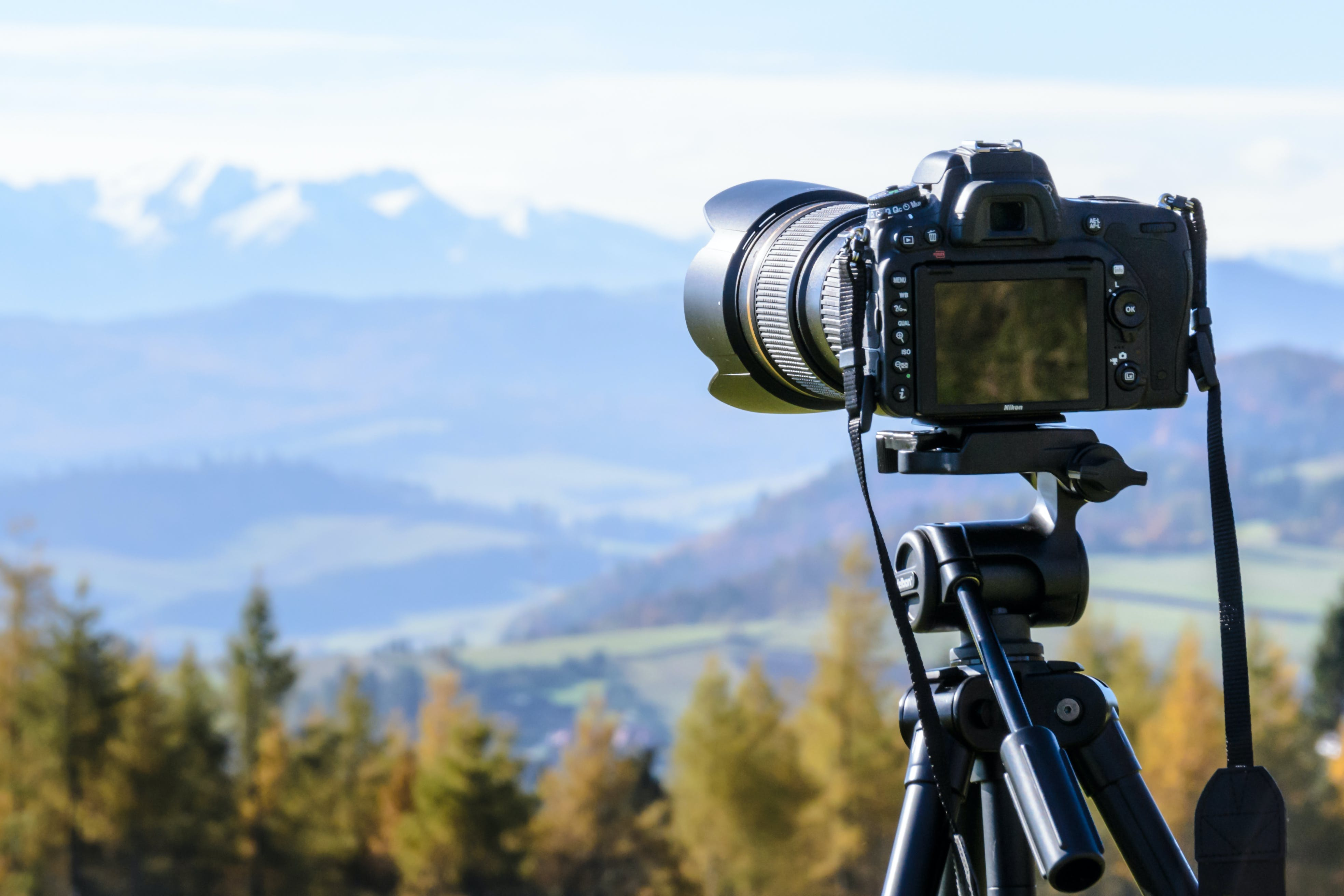 Black Dslr Camera Mounted on Black Tripod