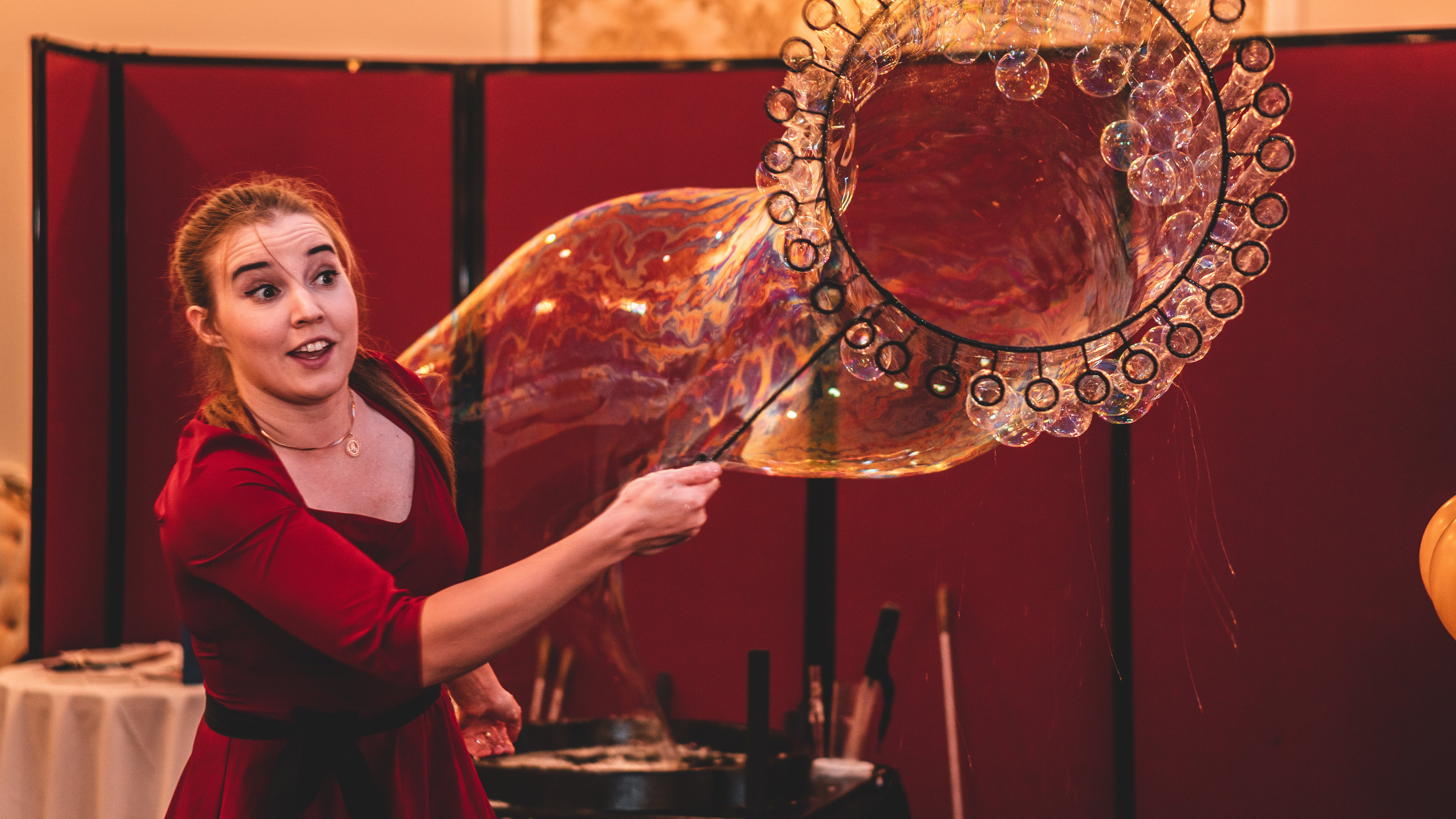 Woman Wearing Red Top Making Giant Bubble