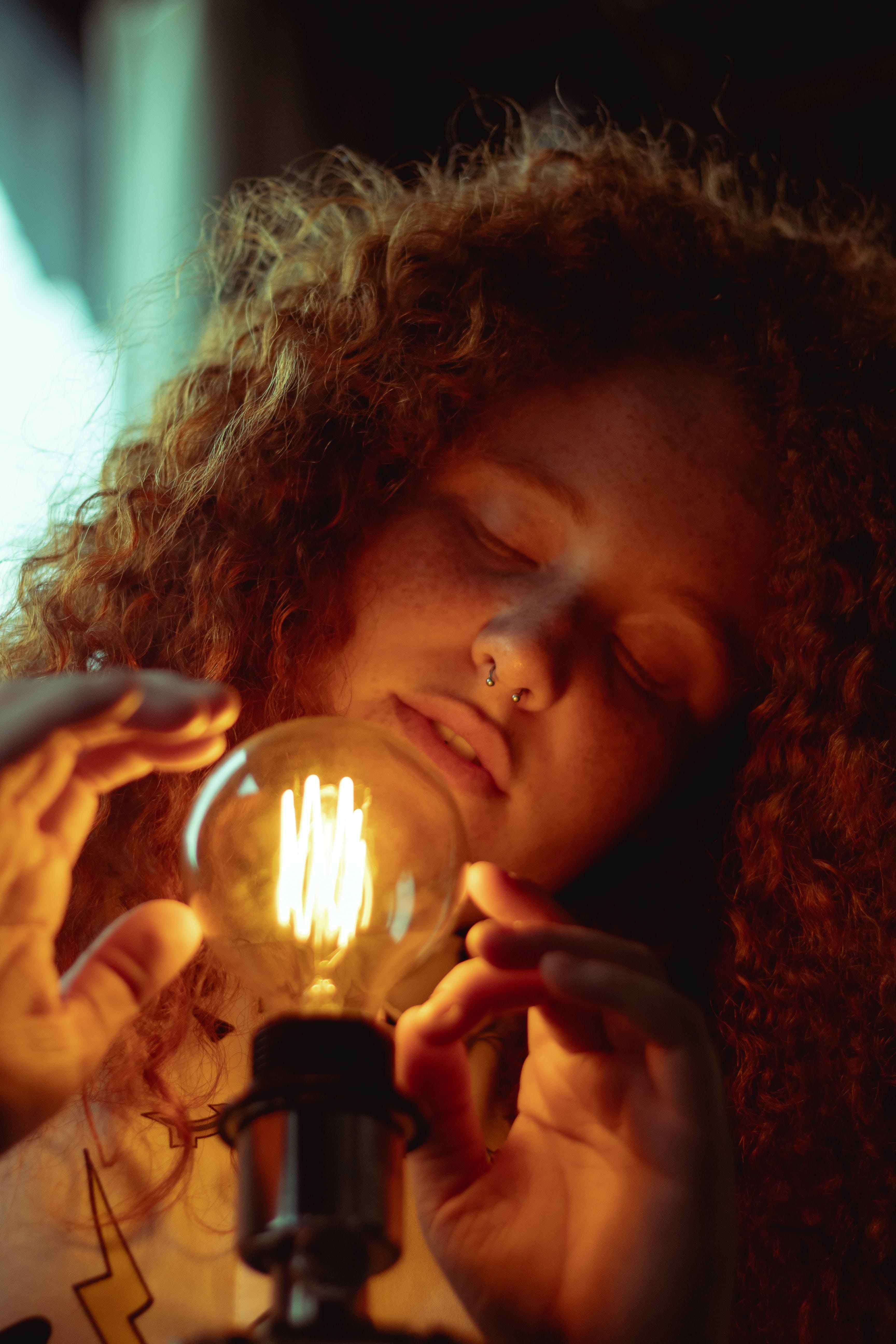 Kostenloses Stock Foto zu beleuchtet, frau, licht, lockig