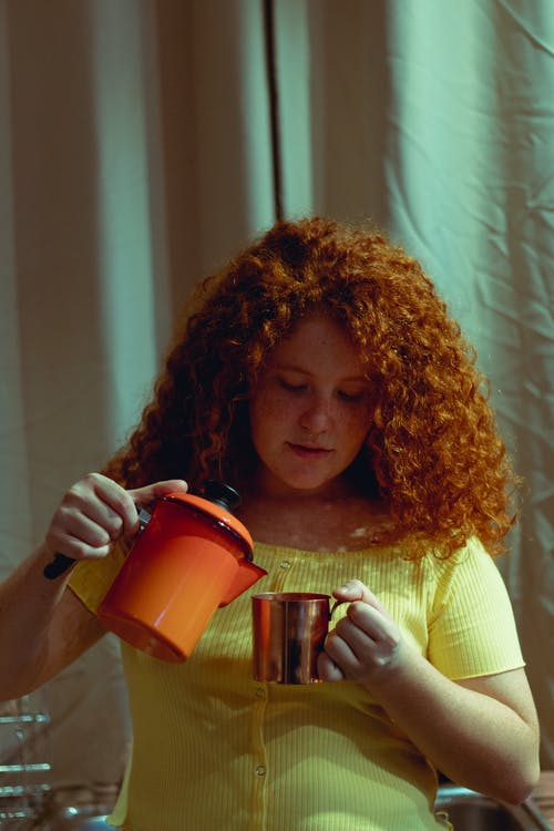 Woman Holding Orange Pitcher