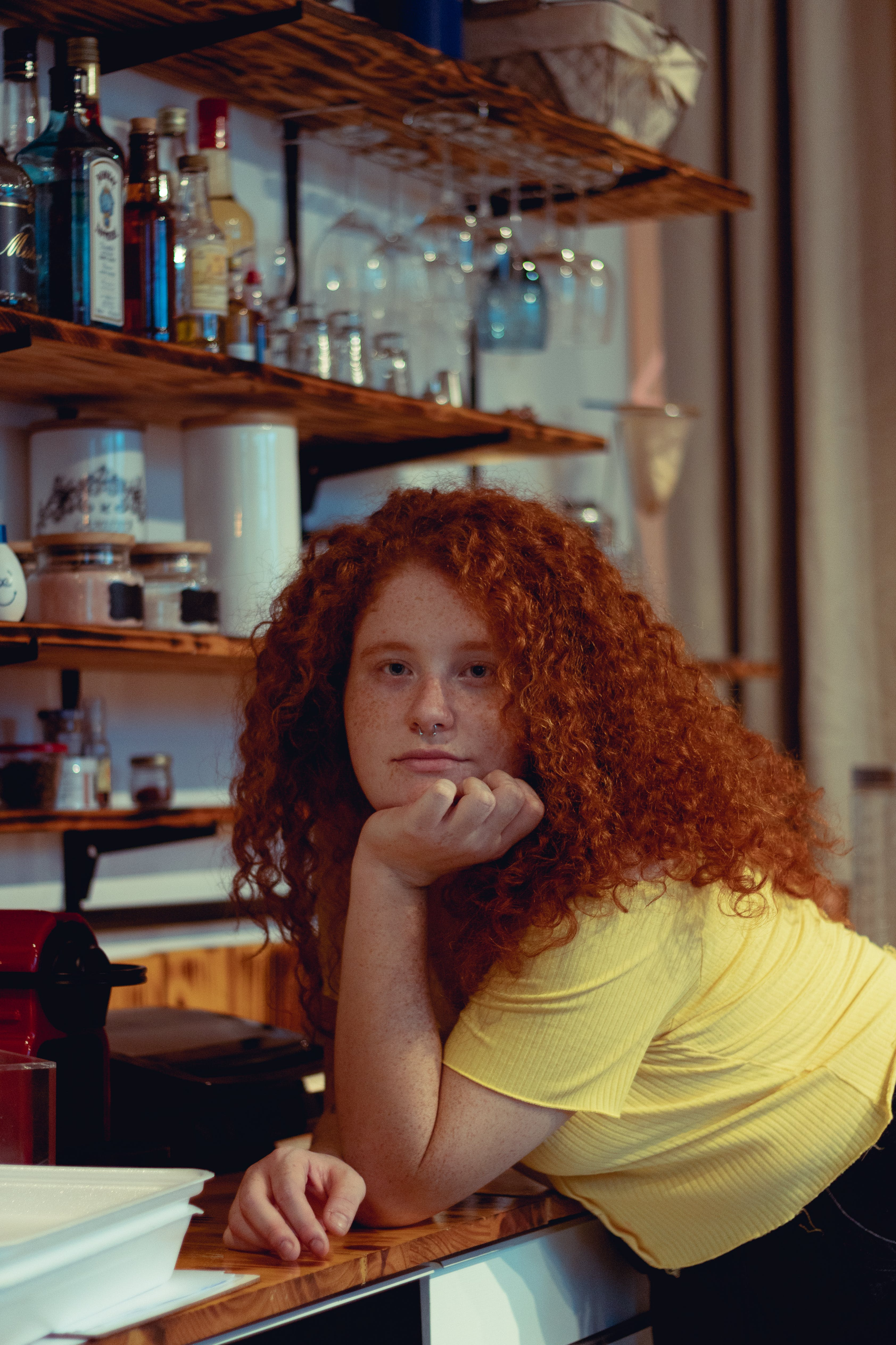 Curly Haired Woman Leaning On Bar Counter