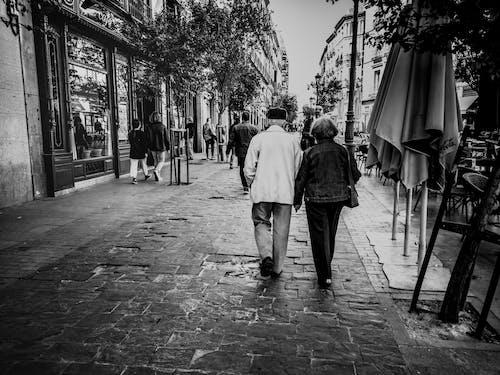 Foto d'estoc gratuïta de ancians, blanc i negre, caminant, carrer