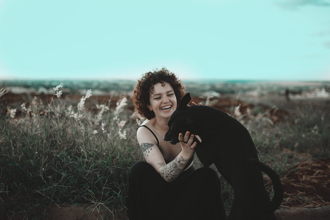 Photo of Smiling Woman Petting Black Dog