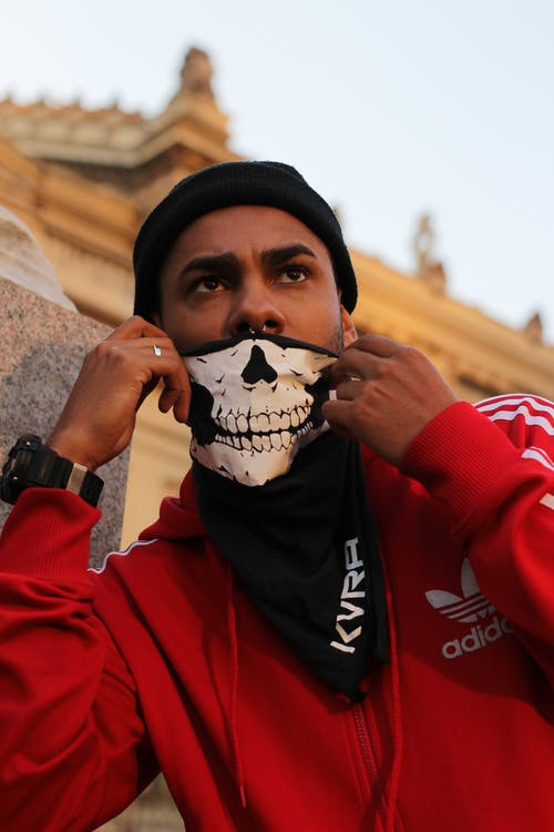 Man Covering His Face With Skull Mask