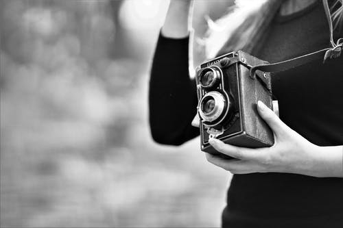 Grayscale Photo of Woman Holding Vintage Camera