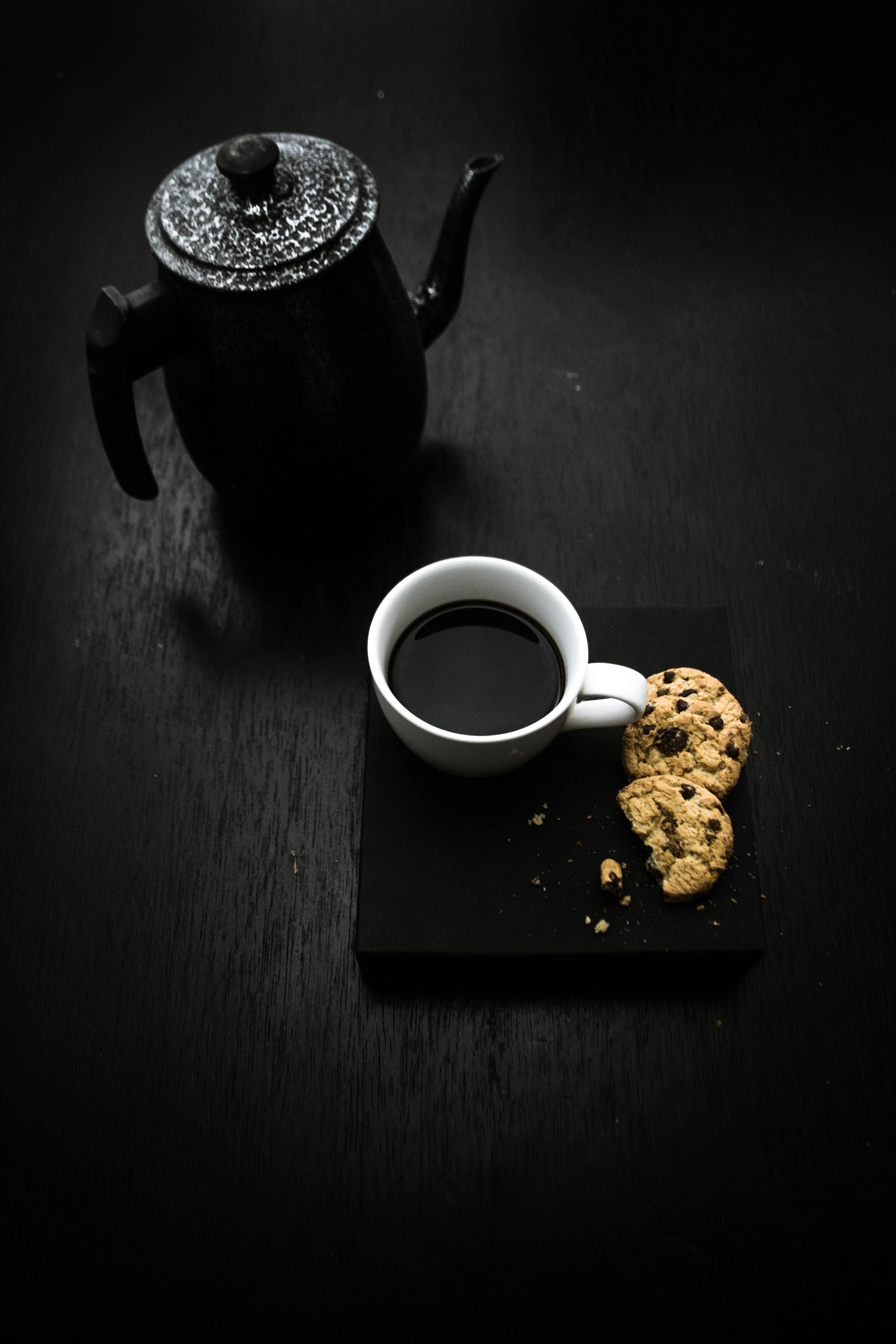 Black Teapot Beside Teacup