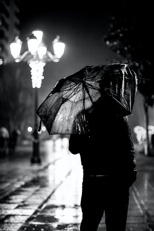 Grayscale Photography of Person Holding Umbrella Beside Post